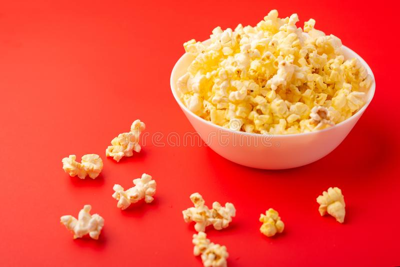 Plate with popcorn on a red bright background. movie viewing concept, weekend getaway, with space royalty free stock photo