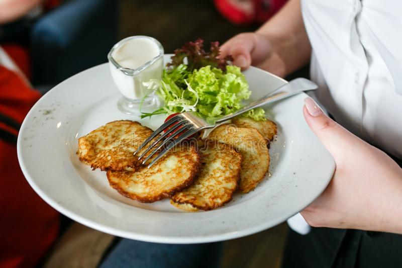 A plate of potato pancakes in the hands of a waiter stock photos