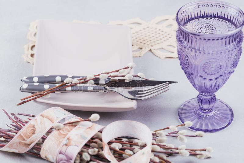 Plate, purple glass, cutlery and willow twigs royalty free stock image