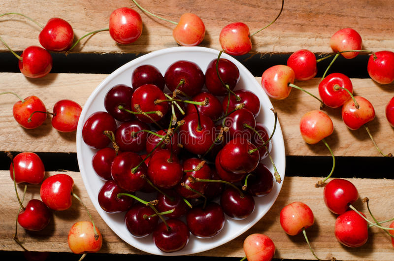 Plate with red cherries on wooden plates, yellow and red cherry, top view.  royalty free stock photo