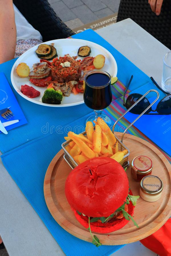 Plate of red tuna with its vegetable garnish and red hamburger in a restaurant. Plate of red tuna with its vegetable garnish and red hamburger, vine glass and royalty free stock photo