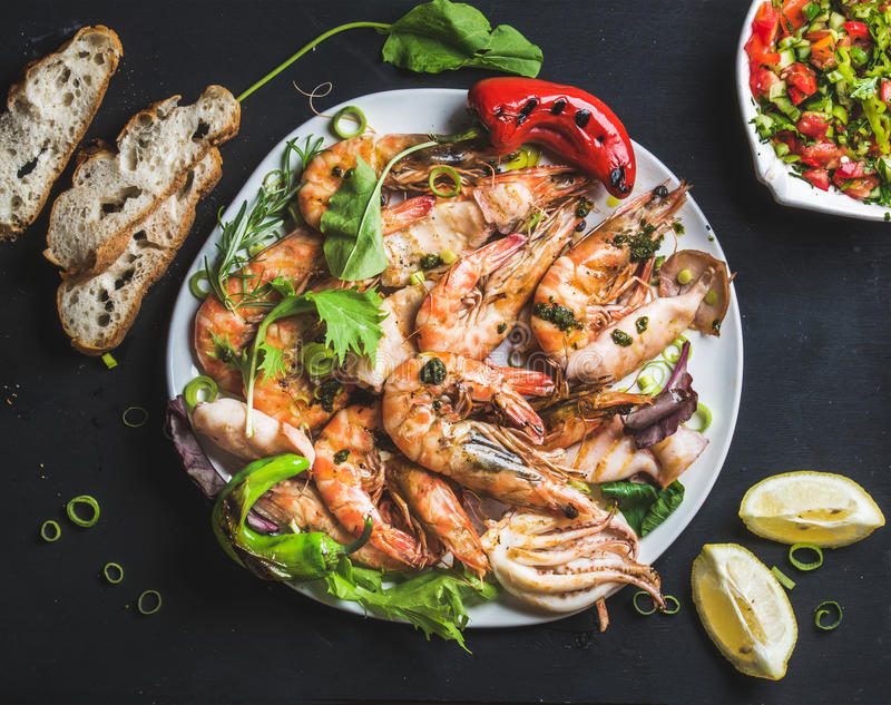 Plate of roasted tiger prawns and octopus pieces with fresh leek, salad, peppers, lemon, bread, pesto sauce over black royalty free stock photo