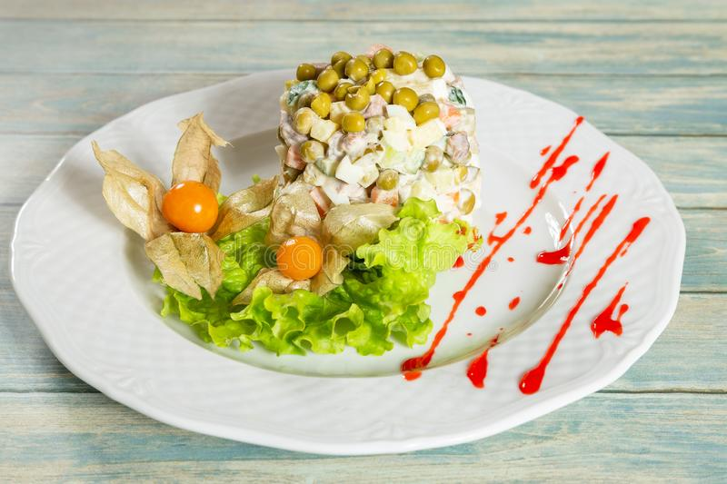 Plate of russian salad with cape gooseberry. On wooden table royalty free stock photo