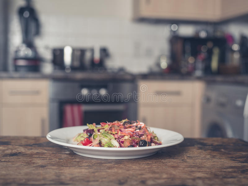 Plate with salad in kitchen royalty free stock image