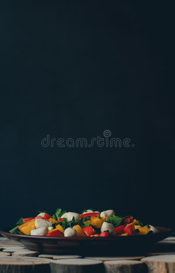 Salad with mozzarella in a clay plate on a wooden background. royalty free stock images