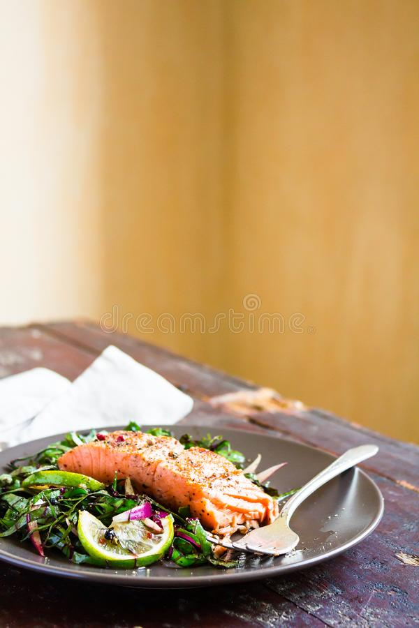 Plate of salmon fillet steak roasted with spices served with fresh salad with lime fruit and peppercorns on a wooden table, select stock images