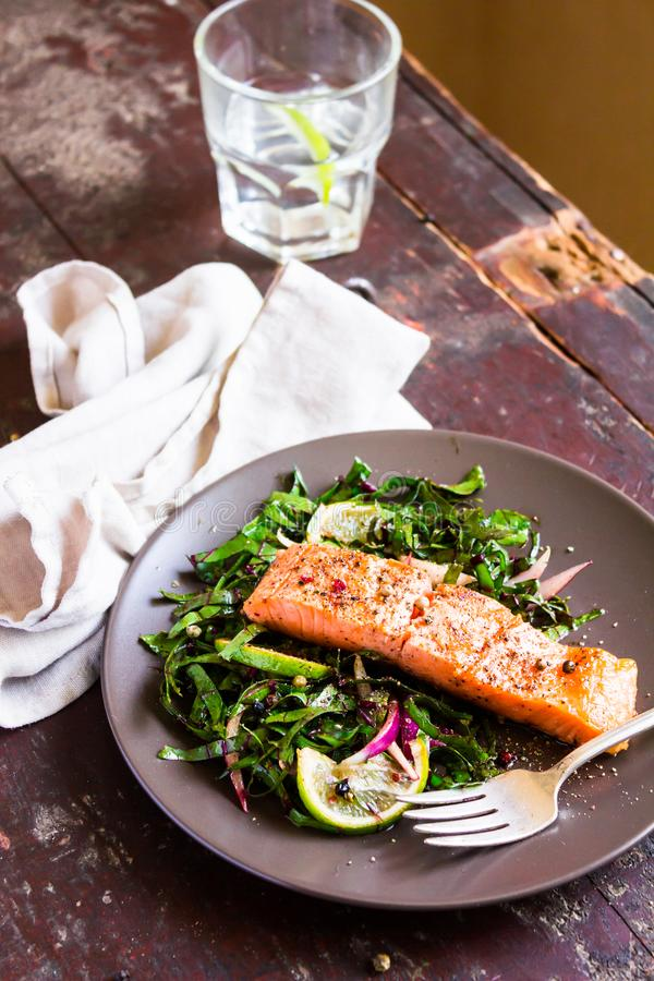 Plate of salmon fillet steak roasted with spices served with fresh salad with lime fruit and peppercorns on a wooden table, select stock photography