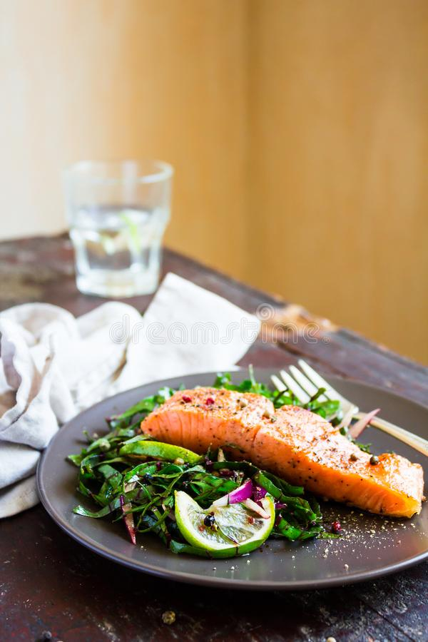 Plate of salmon fillet steak roasted with spices served with fresh salad with lime fruit and peppercorns on a wooden table, select stock image
