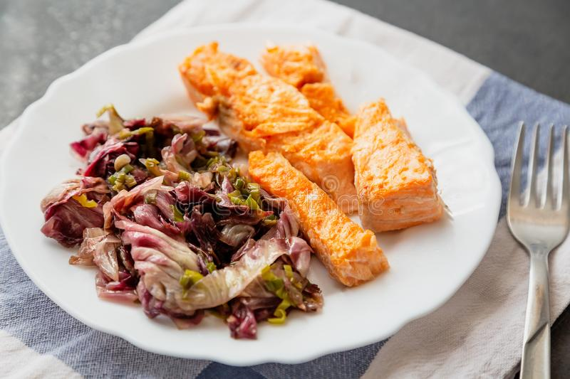 plate with salmon and red radicchio garnish stock photos