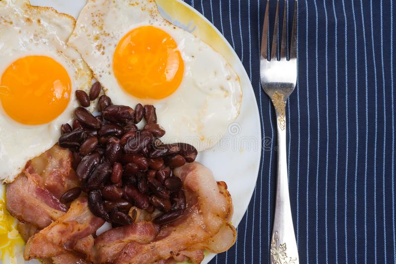 Plate with scrambled eggs, bacon and beans on a wooden rustic table. stock photos