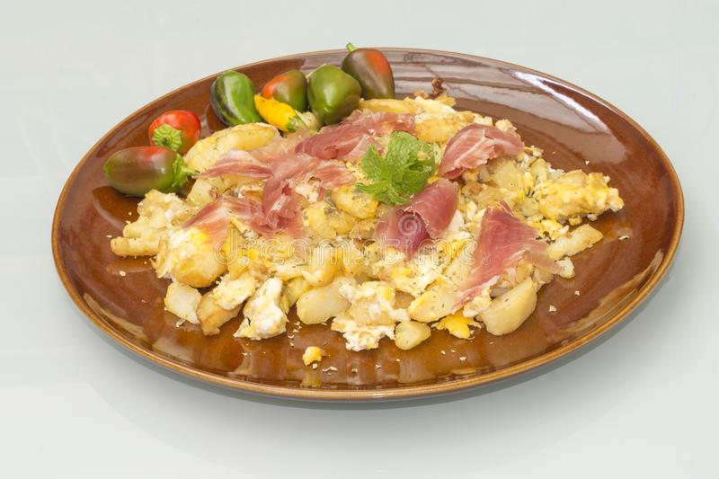 A plate of scrambled potatoes with eggs and ham royalty free stock photography