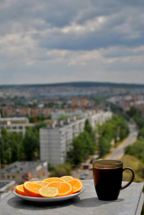 A plate with sliced ​​orange and lemon and a mug of black tea on the background of a blurred panorama of the morning city. A plate with sliced stock photos