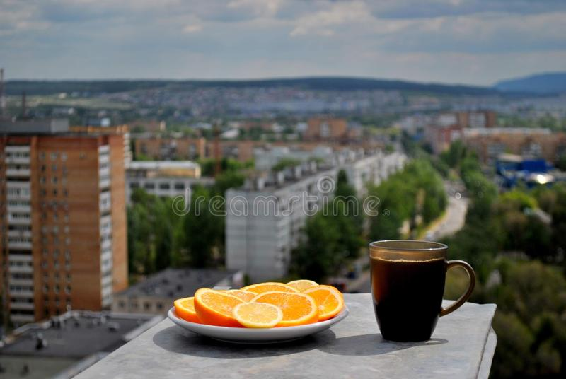 A plate with sliced ​​orange and lemon and a mug of black tea on the background of a blurred panorama of the morning city. A plate with sliced royalty free stock image
