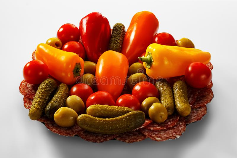 A plate of smoked sausage and vegetables. On a plate there are olives, pickled cucumbers, cherry tomatoes, mini peppers stock images