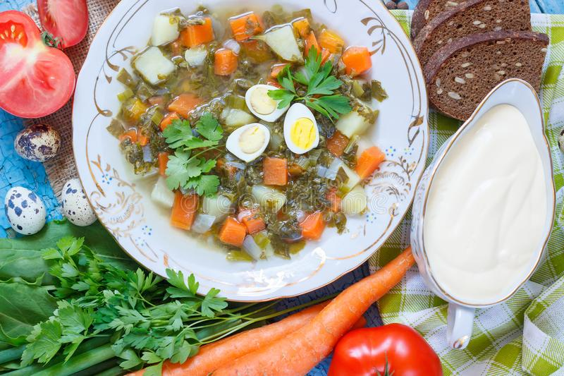 Plate with sorrel soup, bread and different vegetables. Soft focus background royalty free stock photography