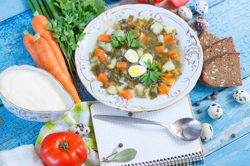 Plate with sorrel soup, bread and different vegetables. Top view royalty free stock images