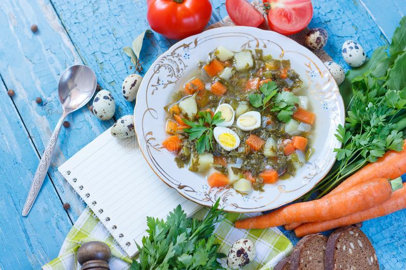 Plate with sorrel soup, bread and different vegetables. Top view stock image