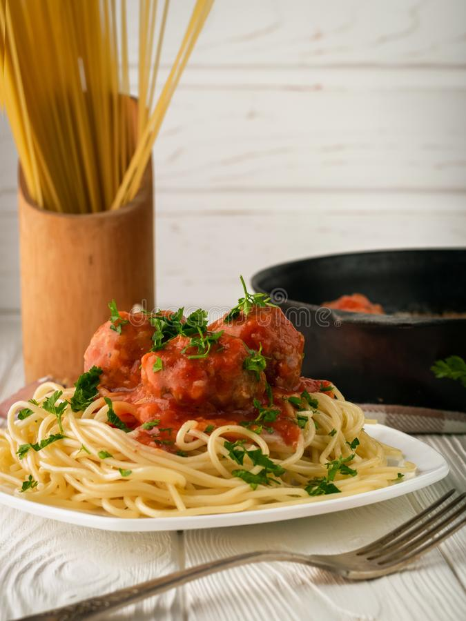 A plate of spaghetti with meatballs in tomato sauce and raw spaghetti vertical shot with copy space royalty free stock photo