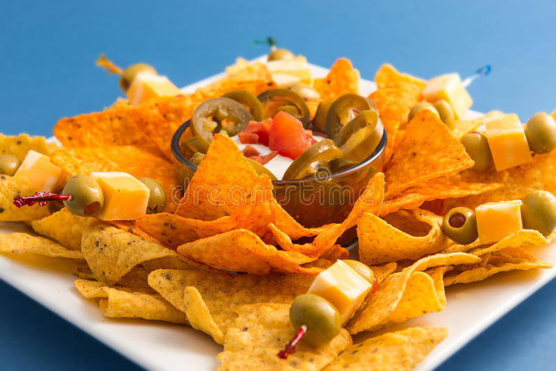 Plate of Spicy Nachos. Spicy mexican nachos over a blue background. Delicious junk food. Special for a snack while drinking beer stock images