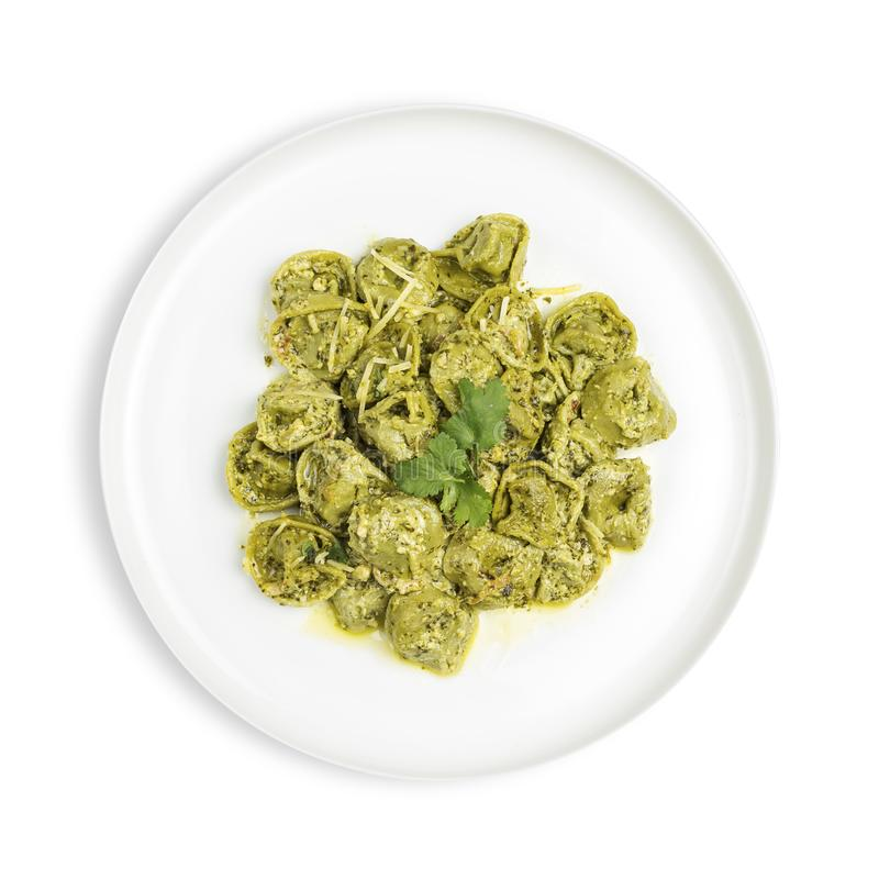 Plate of spinach tortellini in creamy pesto sauce isolated on white stock photography