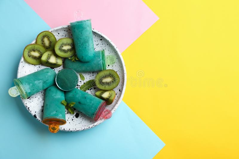 Plate with spirulina popsicles, mint and kiwi slices on color background, top view. stock photos