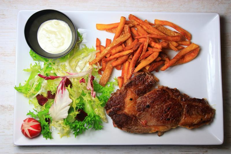 Plate of steak with french fries and lettuce salad. And sauce stock photos