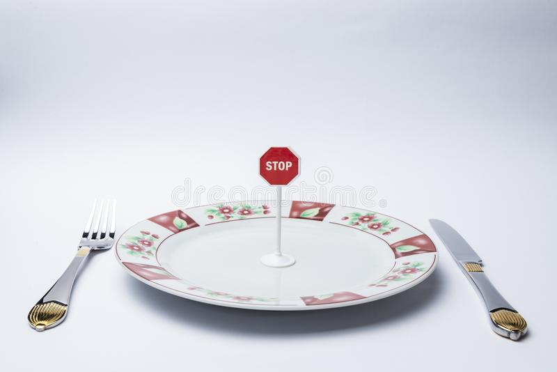 On the plate a stop sign. Fork, knife, plate on white background, and on the plate a stop sign stock photography