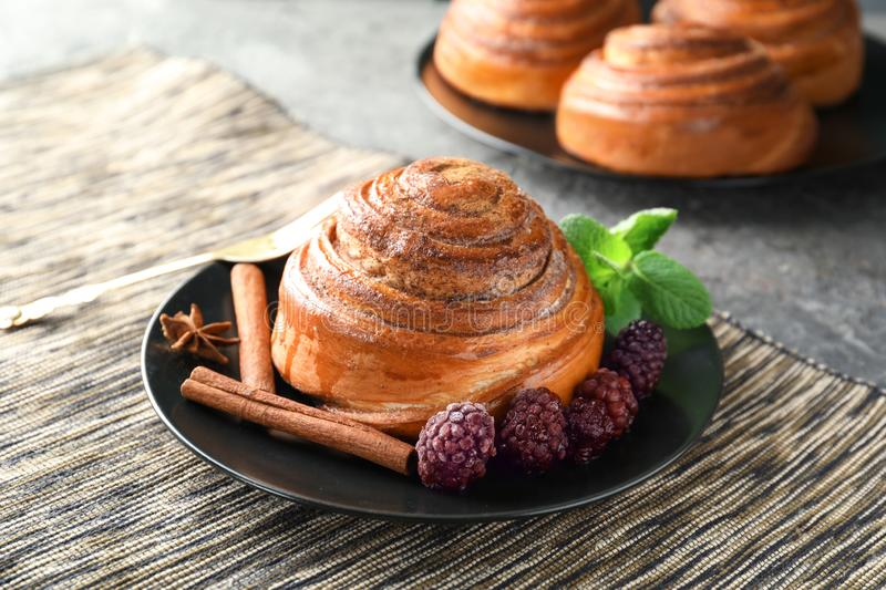 Plate with sweet cinnamon bun and berries on table royalty free stock photography