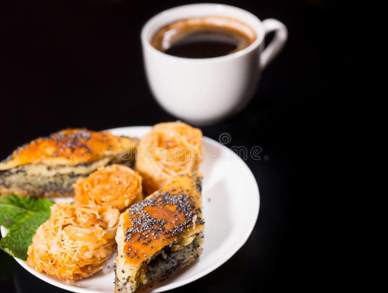 Plate of Sweet Pastries with Black Coffee on Black. Close Up of Plate Filled with Poppy Seed and Other Pastries on Black Counter with Cup of Mug of Black Coffee royalty free stock photography