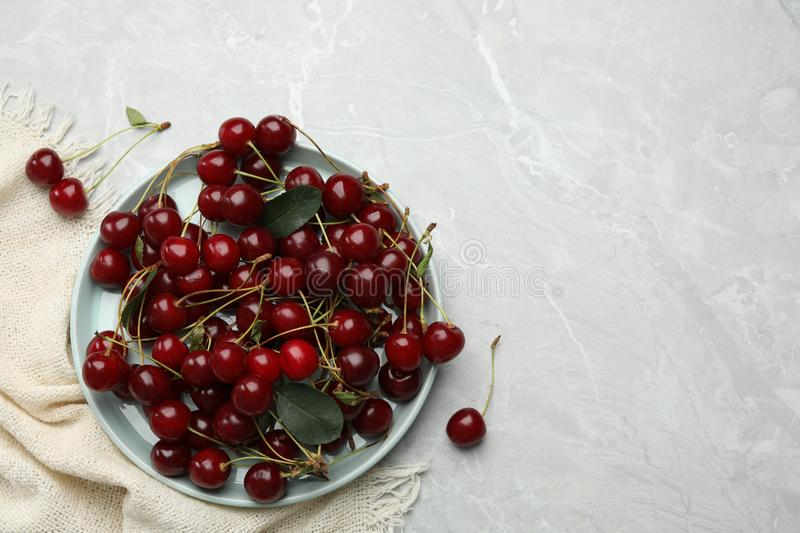 Plate of tasty cherries and fabric on grey marble table, space for text stock images
