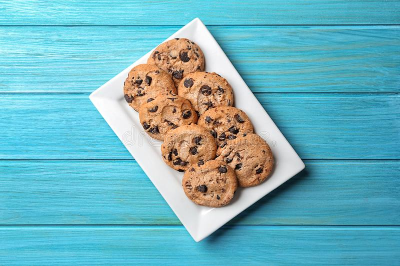 Plate with tasty chocolate chip cookies on color wooden table, top view royalty free stock photo