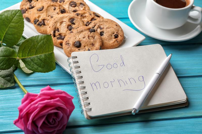 Plate with tasty chocolate chip cookies, cup of coffee and GOOD MORNING note in notebook on color wooden table stock photo