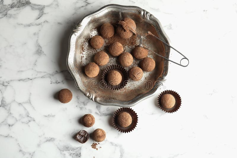 Plate and tasty chocolate truffles on marble background stock images