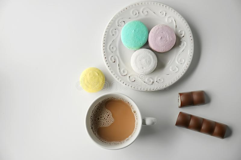 Plate with tasty colorful macarons and cup of coffee on white background stock photo