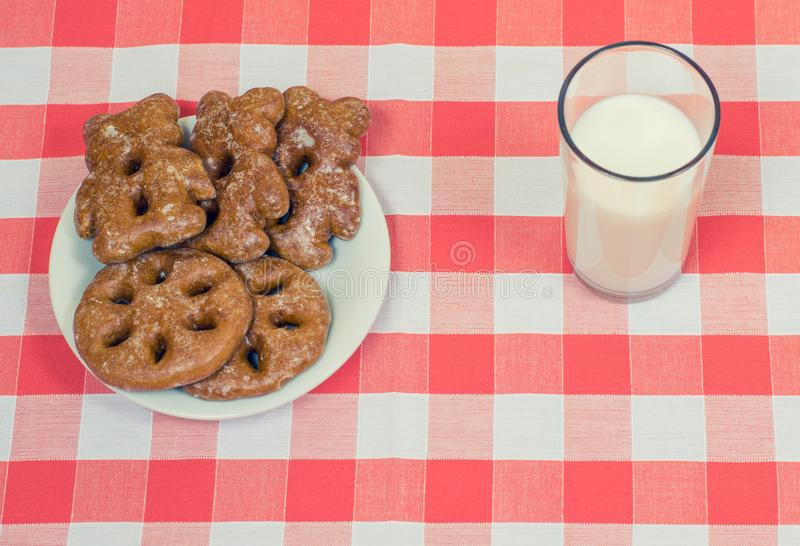 Plate with tasty cookies and glass of milk on checkered tablecloth stock images