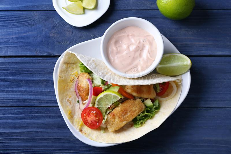 Plate with tasty fish taco and sauce royalty free stock image