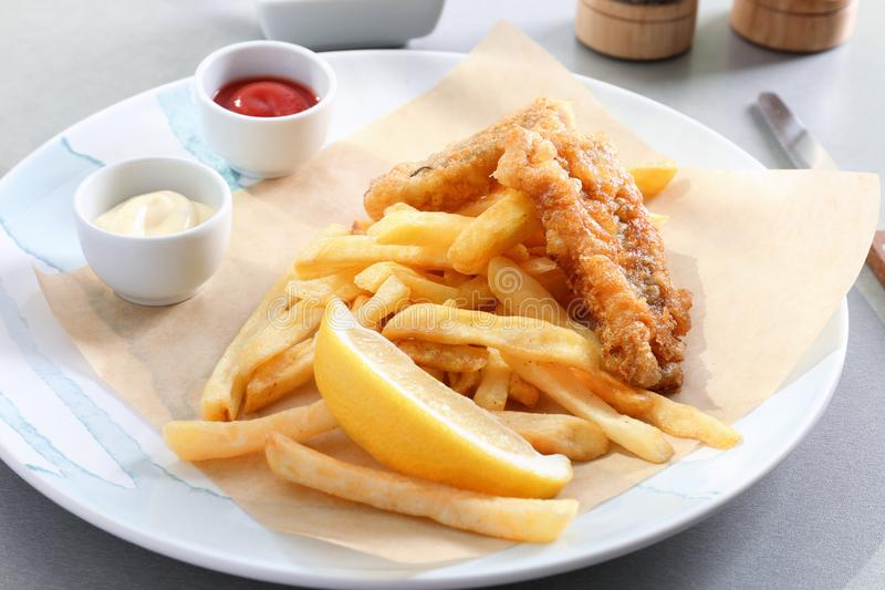 Plate with tasty fried fish, chips and sauces on table royalty free stock photos