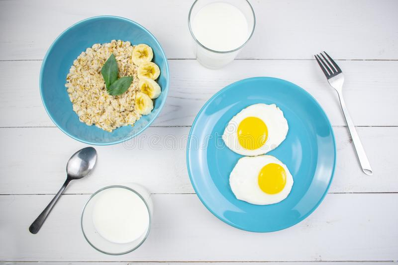 Plate with tasty oatmeal and banana slices and fried eggs on white wood background. Concept image of breakfast, healthy stock images