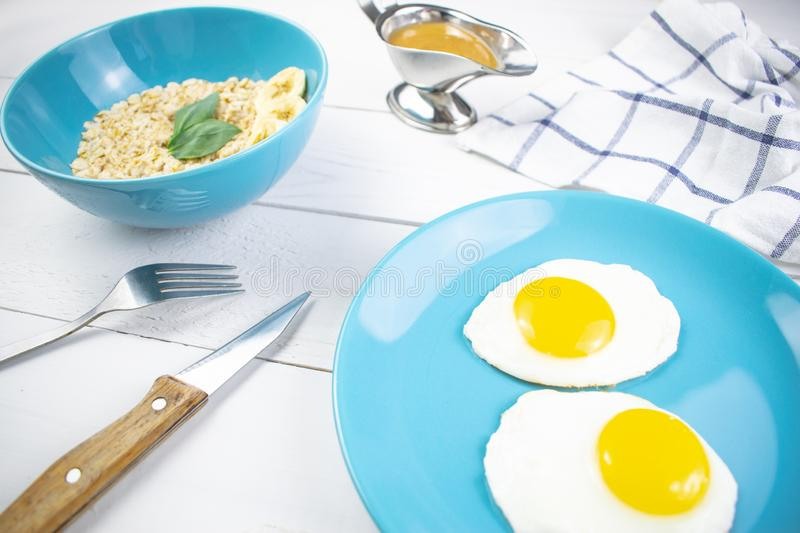 Plate with tasty oatmeal and banana slices and fried eggs on white wood background. Concept image of breakfast, healthy stock image