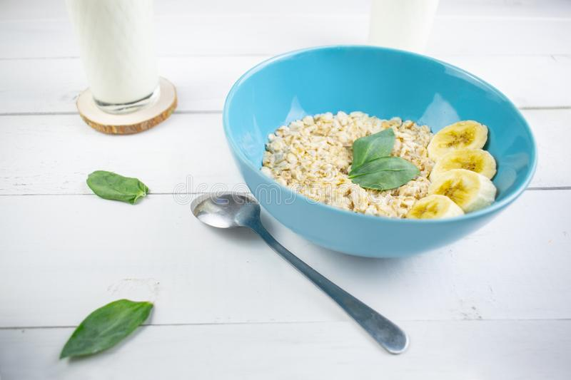 Plate with tasty oatmeal and banana slices on white wood background. Concept image of breakfast, healthy eating. royalty free stock photo