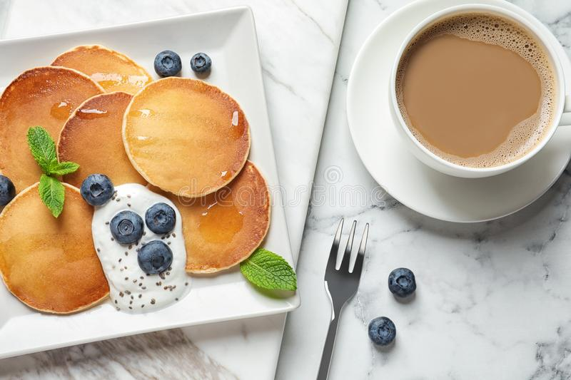 Plate of tasty pancakes with blueberries, sauce and mint on white marble table. Flat lay royalty free stock images