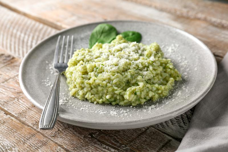 Plate with tasty spinach risotto on table, stock images