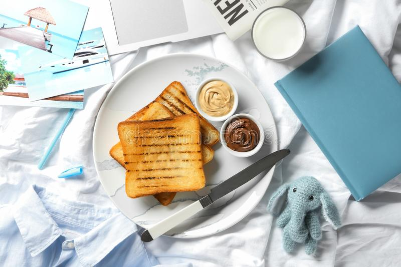 Plate with tasty toasts and glass of fresh milk on bed royalty free stock photo