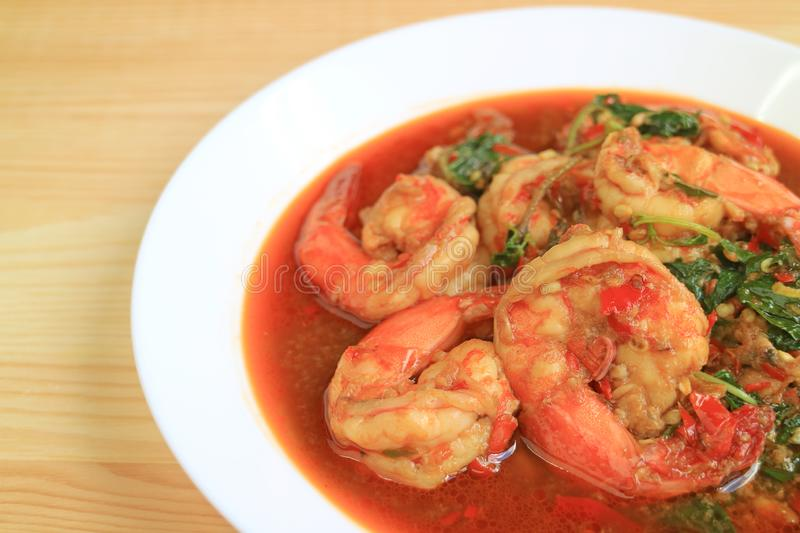 Plate of Thai Style Spicy Stir Fried Prawns with Holy Basil Served on Wooden Table. Texture background asian beige blurred chili closed copy cuisine delicious royalty free stock photo