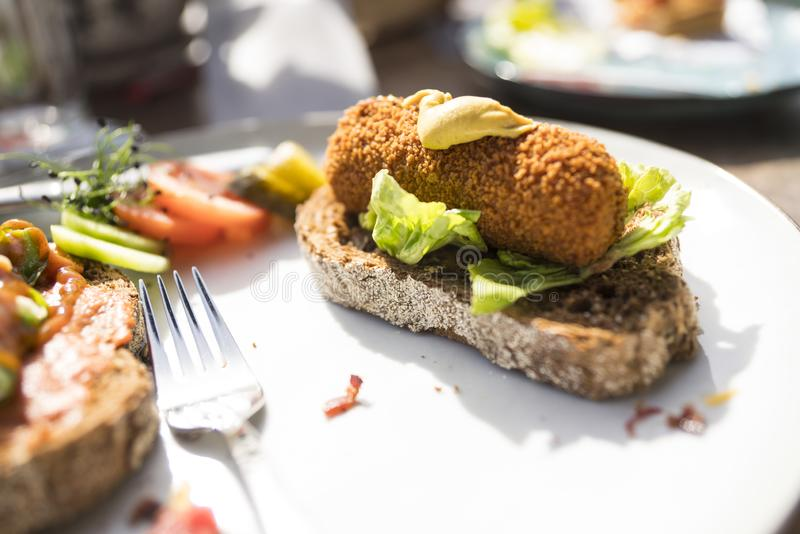 Plate with typical Dutch meal, fried snack croquet with salad on slice of bread royalty free stock photo
