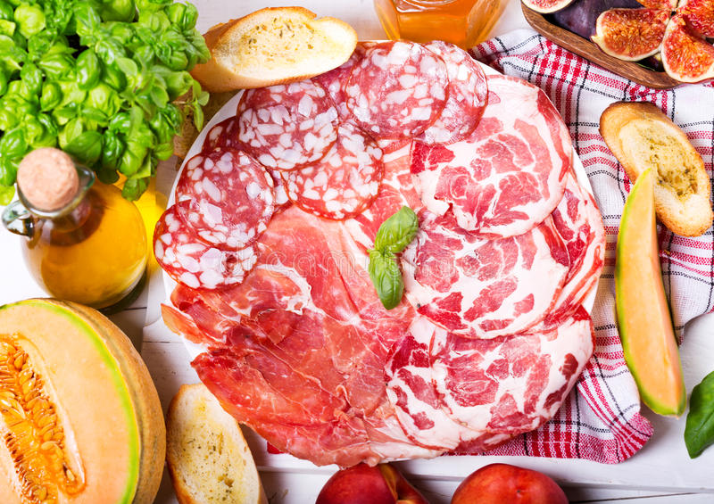 Plate of various ham and salami with fresh fruits royalty free stock photos