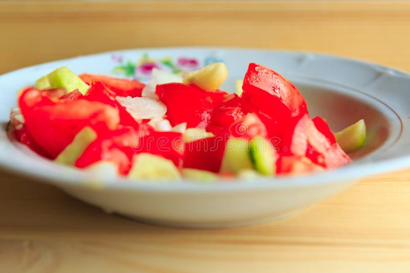 Plate of vegetable salad with fresh tomatoes and cucumbers royalty free stock photography