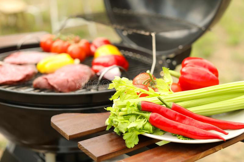 Plate with vegetables near barbecue grill outdoors. Closeup stock photos