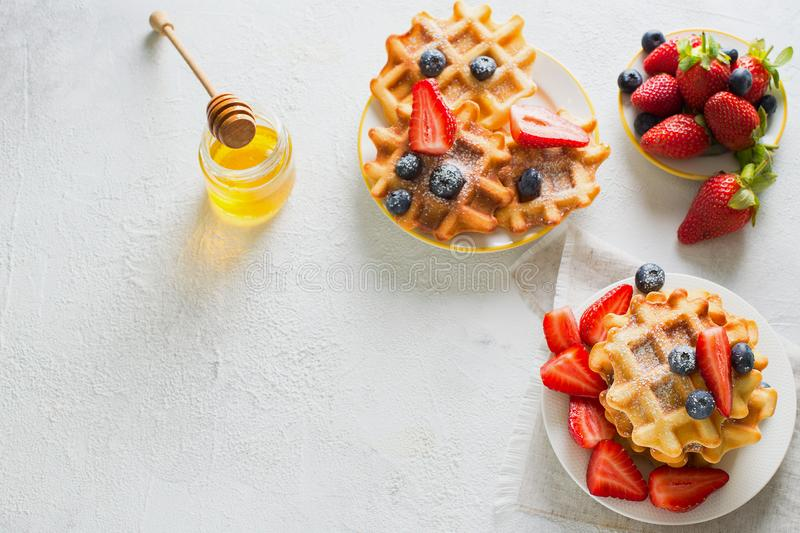 Plate with waffles with strawberries and blueberries and cup of. Tea on grey texture stock photos