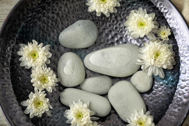 Plate of water with flowers and stones prepared for pedicure treatment in spa salon, closeup stock photos